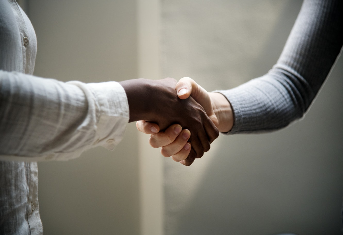 Stock photo of two people shaking hands. Caption: I really, really want an internship