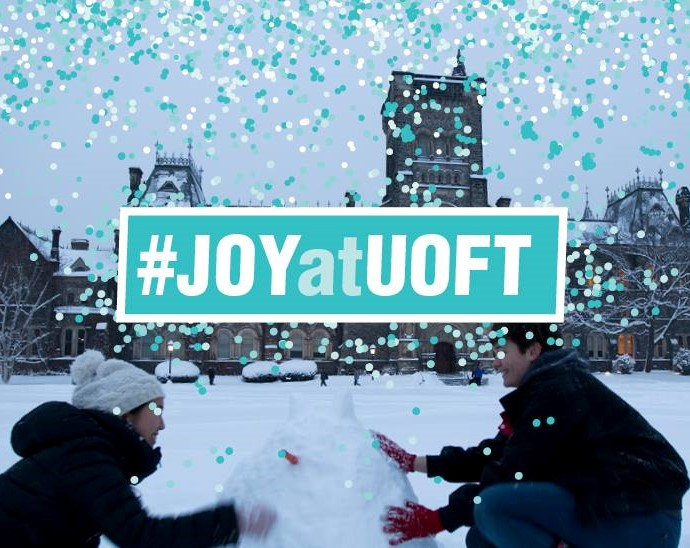 An image of two people building a snowman on front campus, with the blue words #JoyAtUOfT.
