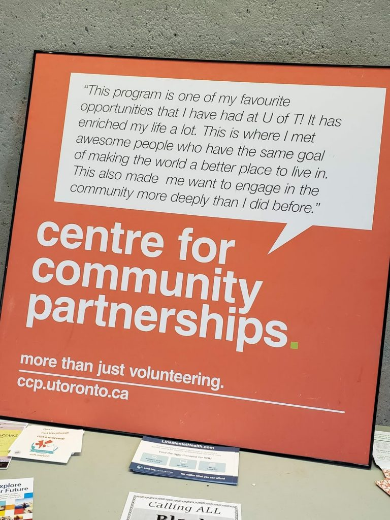 "An orange and white poster with text, title being: ""centre for community patnerships"""