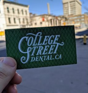Somebody holding a College Street Dental card in front of the street.