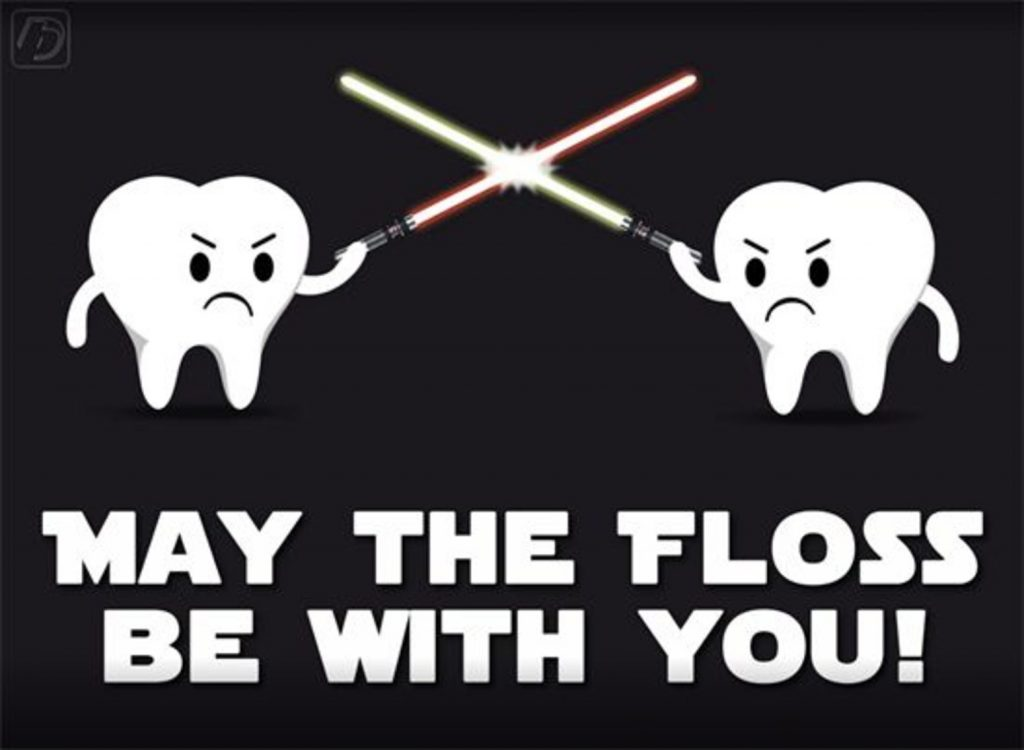 "Two teeth fighting with light sabers, captioned ""May the floss be with you!"""