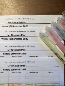 Four mock timetables with highlighters spread out on a table