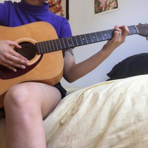 A person sitting on a bed holding a guitar.
