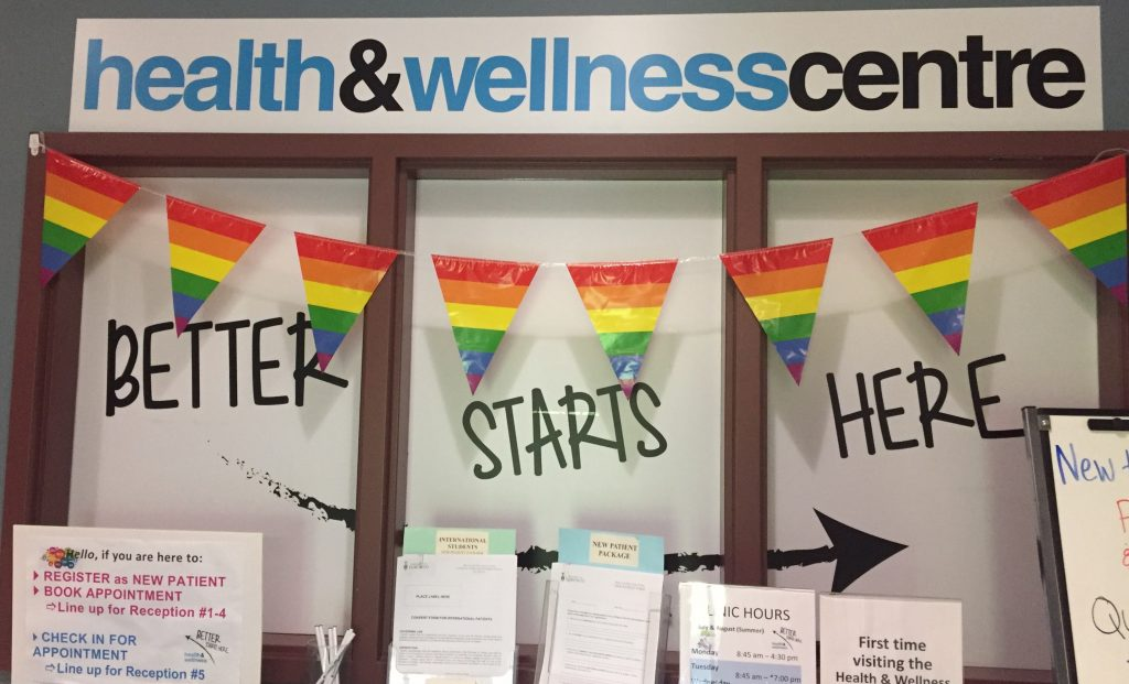 "A sign that says: ""health & wellness centre: better starts here"" with rainbow pride flags"