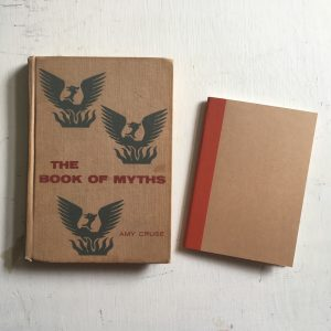 "Front cover of ""The Book of Myths"" beside a small notebook."