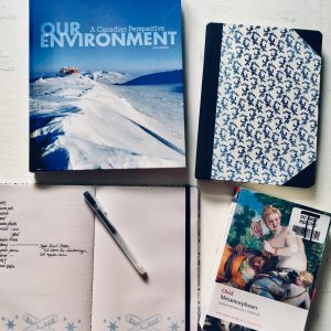 "An Environment textbook, two notebooks, and ""Metamorphoses"" by Ovid."