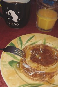 Two pancakes stacked on a plate with butter and maple syrup. There is also a mug and a cup with juice behind the plate