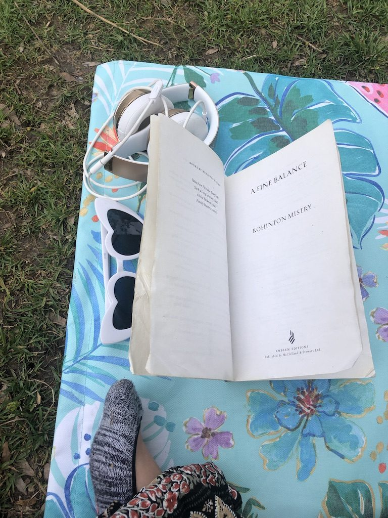 A book, a pair of sunglasses and headphones on a towel on the grass.