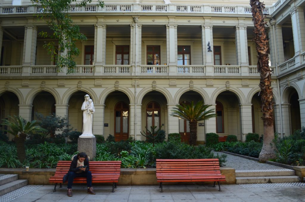 a woman is seated on a bench, texting, in one of the quads of the Catholic University in Santiago