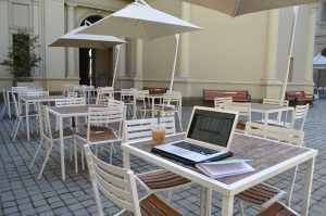Empty tables and chairs outside. On the table closest to the camera there is a laptop and coffee.