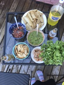A table setup with homemade guacamole, pico de gallo, tamales, and a bottle of soda. There is also a pot of cilantro