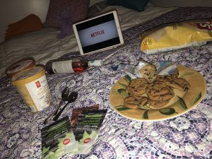 On a bed we see many snacks, face masks, and Netflix open on an Ipad