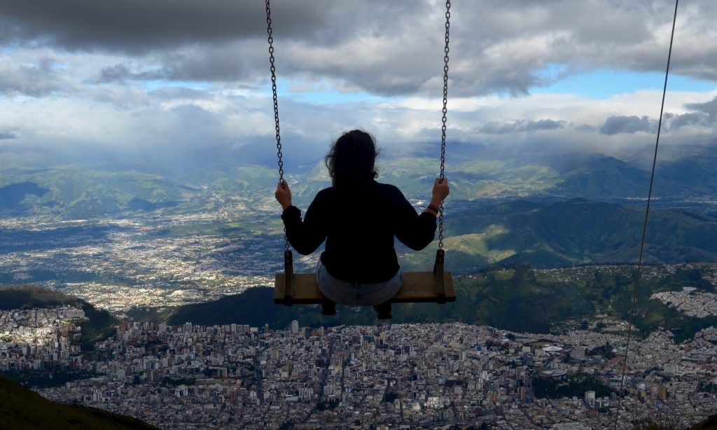 Swinging on a swing on the side of the Pichincha volcano which overlooks Quito, Ecuador