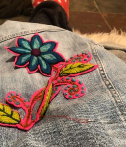 A pink and blue flower patch being sown onto jean.