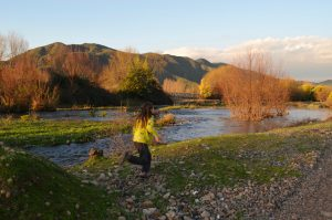girl running along a river. A dirt road peeks into the foregound while mountains occupy the background