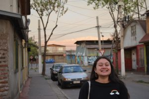 Girl in the foreground smiling with her entire face in a neighbourhood in Santiago