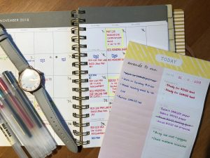 Picture of my agenda and to do list with a watch and some pens on the side