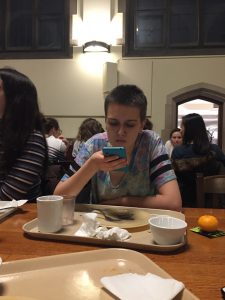 A person sits in a dining hall, looking at their phone.
