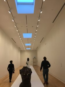 Two people walking away from the camera in an art gallery