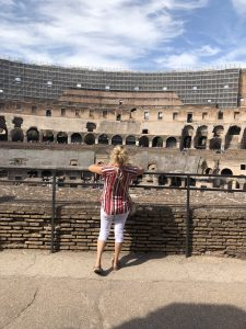 My mom stands by a metal fence looking into the Colloseum in Rome