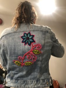 The back of a jean jacket with a flower patch