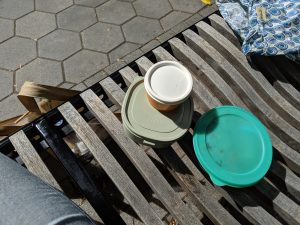 Three reusable food containers on a park bench