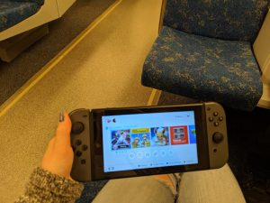 Hand holding portable video game console with train seats in background