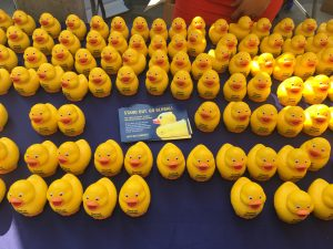 Yellow stress ball duckies on blue table with a GO GLOBAL flyer on centre of table