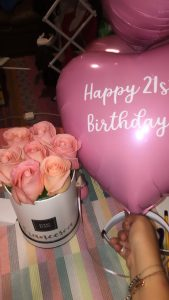 A bouquet of pink roses in a white container and a pink heart-shaped balloon that says Happy 21st Birthday