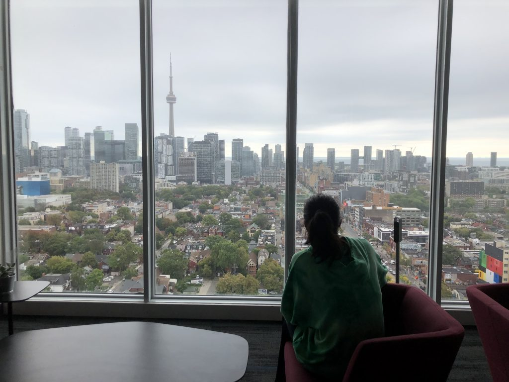 A girl sits by the window of a high-rise building and you can see the skyline in the background.