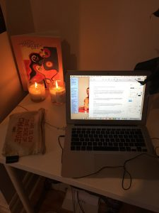 A computer on a desk with candles