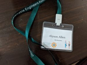 "Dark green lanyard with words ""Sustainable Engineers Association"" with name tag with name, a flower logo, and people on a brown surface"