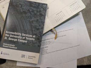 "A pamphlet for ""Accessibility Services at the University of Toronto"" on top of a notebook and some paperwork"