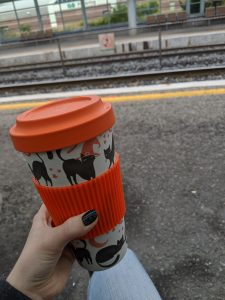 Orange mug with black cats being help in front of train tracks