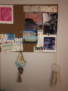 A cork-board with different items pinned on, including pieces of work done b y Francesca.