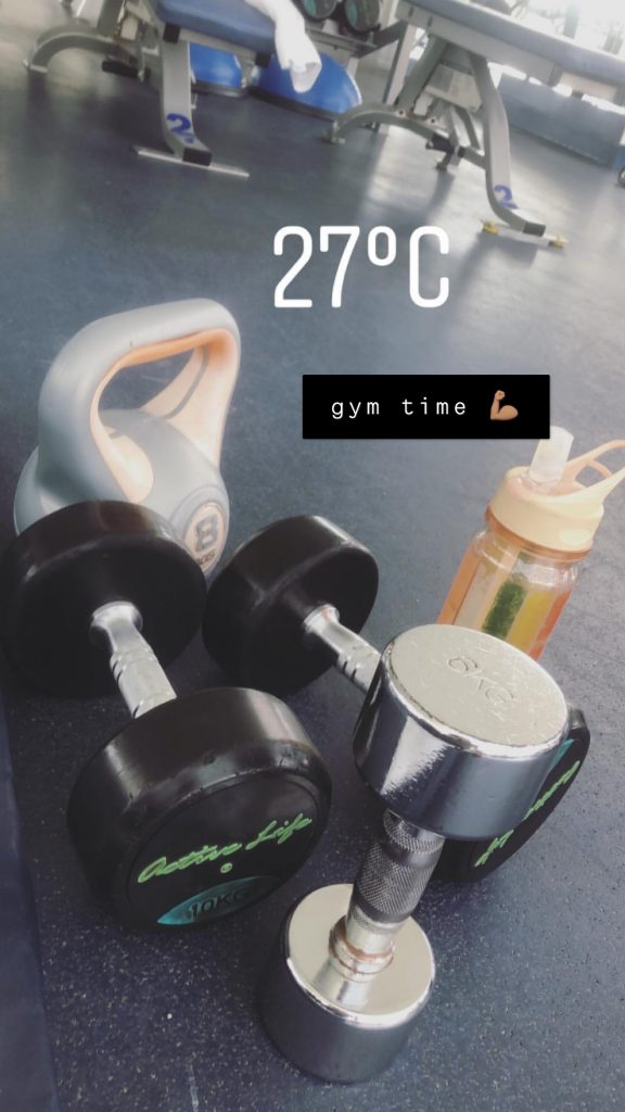 "A couple of dumbells and a water bottle set on the floor. There's a water stamp that reads 27 degrees celcius. There's also text with a black background that reads ""gym time""."