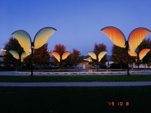 Filtered landscape photograph of a fountain in a park surrounded by banners shaped as wings