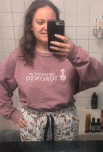 Francesca taking a mirror selfie, making a funny face, wearing a UofT sweatshirt and sweatpants