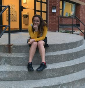 Francesca sitting on the stairs, wearing a yellow shirt under a white top, a black skirt, and black shoes.