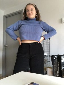 Francesca smiling at the camera, she's wearing a light blue cropped sweater and black pants, as well as geometric earring and a headband.