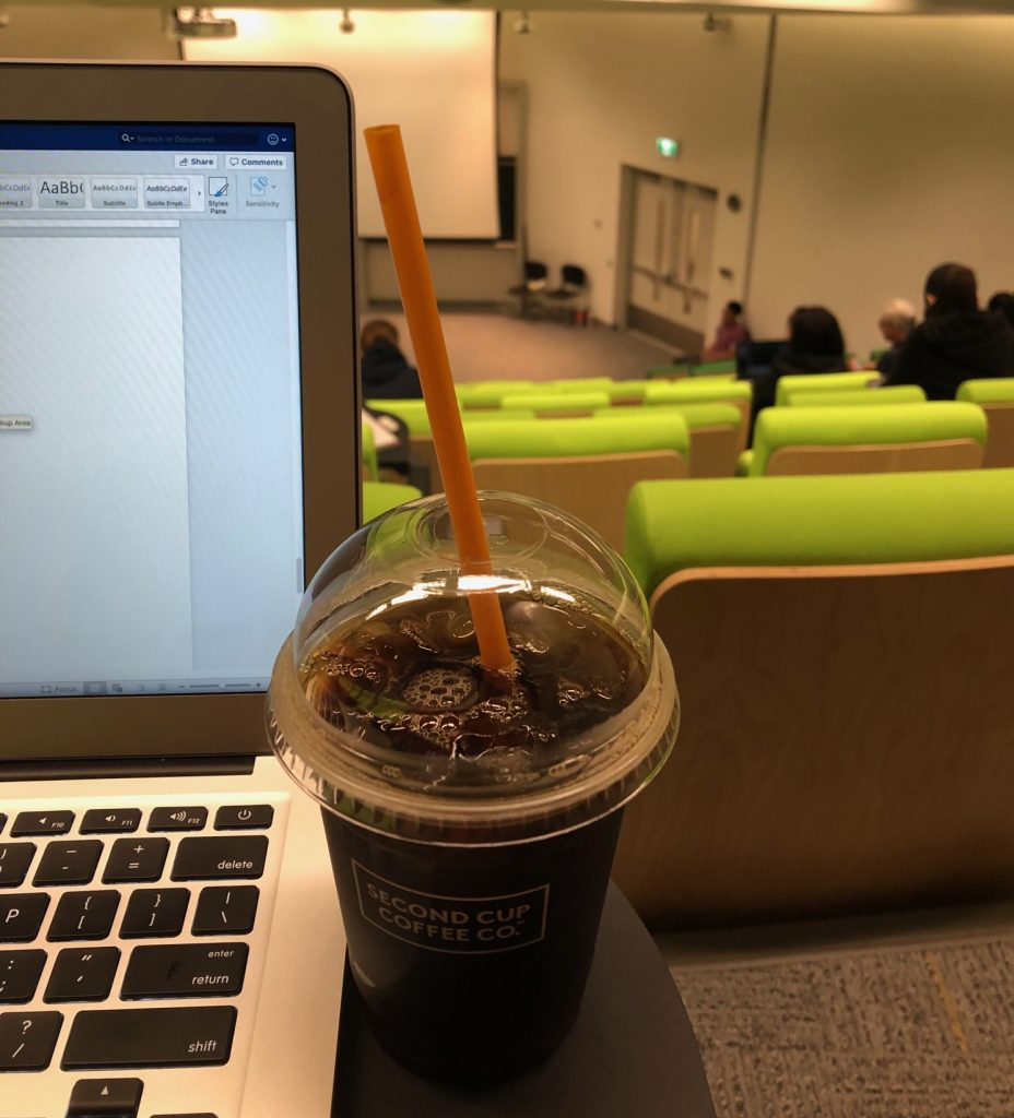 Picture of a cup of coffee, my laptop, and the inside of my lecture hall