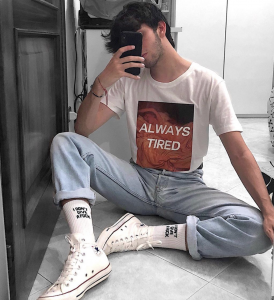 "A man holds his phone up to take a selfie. He's wearing a white shirt that says ""Always Tired"" on it, and he is dressed in the garb of today's youth: white sneakers and jeans folded up above white socks."