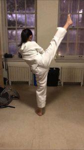 Girl in her taekwondo uniform kicks high in a dorm.