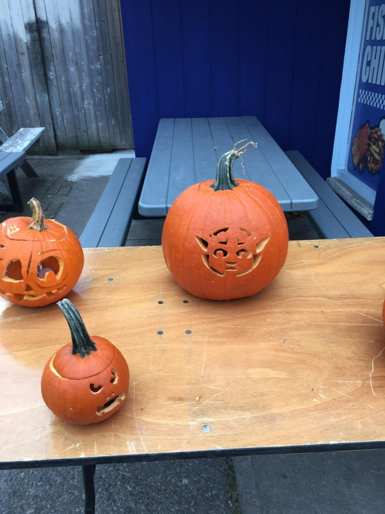 Three carved pumpkins on a table, and one is Yoda.