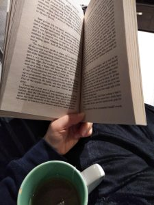 Open book and mug with tea