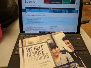 """Booklet with """"We Help Remove Barriers"""" written on it on a laptop open to a UofT website"""