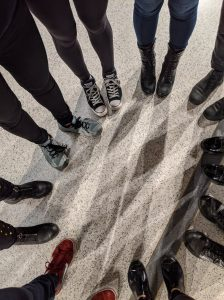 shoes and legs of people lined up in a circle