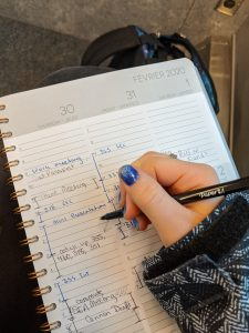 agenda with hand holding a pen