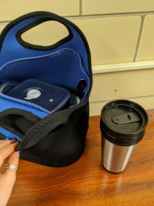 black lunchbag slightly open to show a container inside and thermos on the side