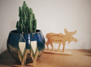 beaded earrings hanging from a potted cactus plant with a carved wooden moose